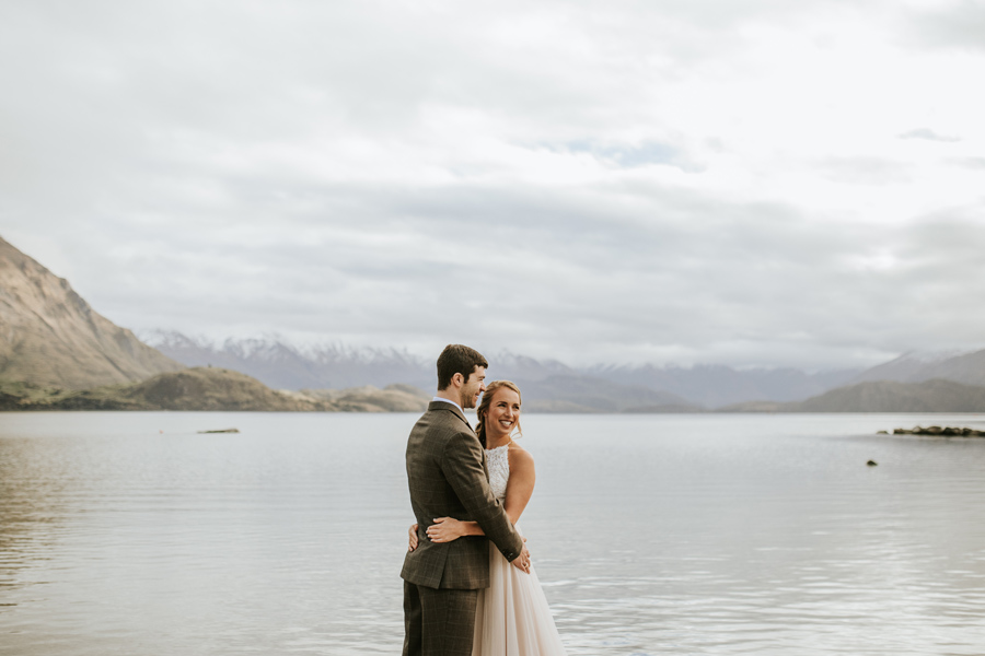A bride and groom embrace infront of Lake Wanaka.