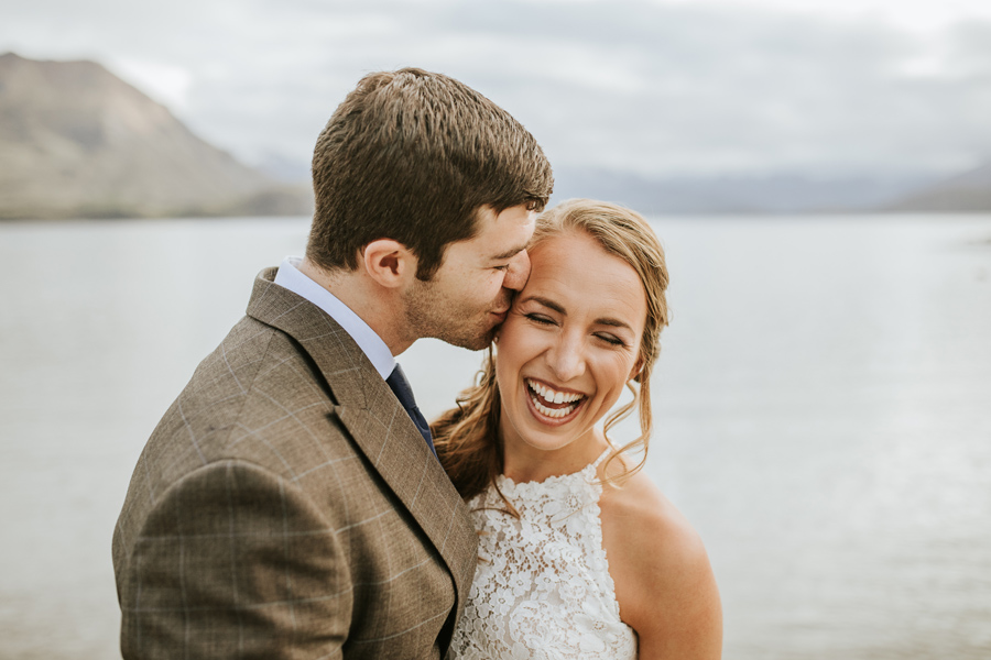 A bride laughs as she is kissed on the cheek by her groom.