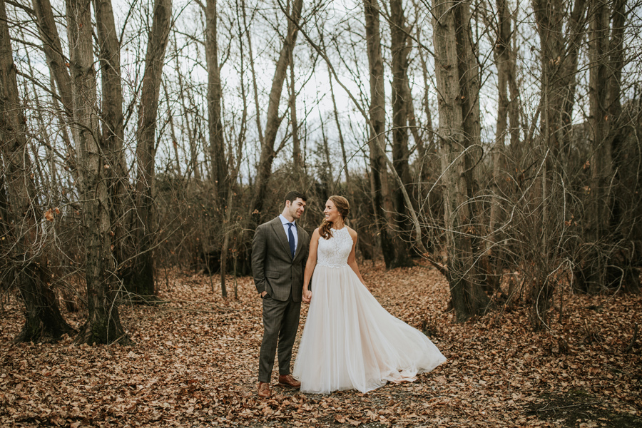 A bride and groom hold hands in the trees. They stand on a blanket of leaves as it is winter and the trees are bare.