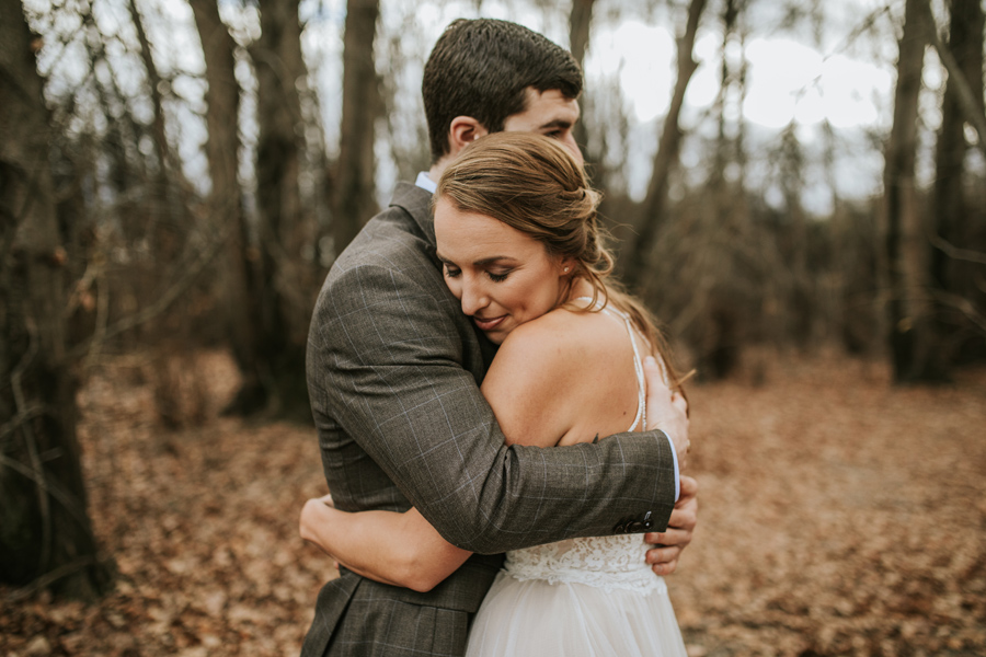 A bride and groom embrace in the trees. With photography by Alpine Image Company.