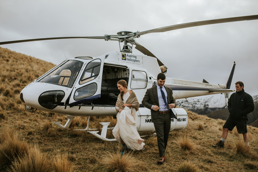 A bride and groom step out of a helicopter. They walk towards the camera laughing.