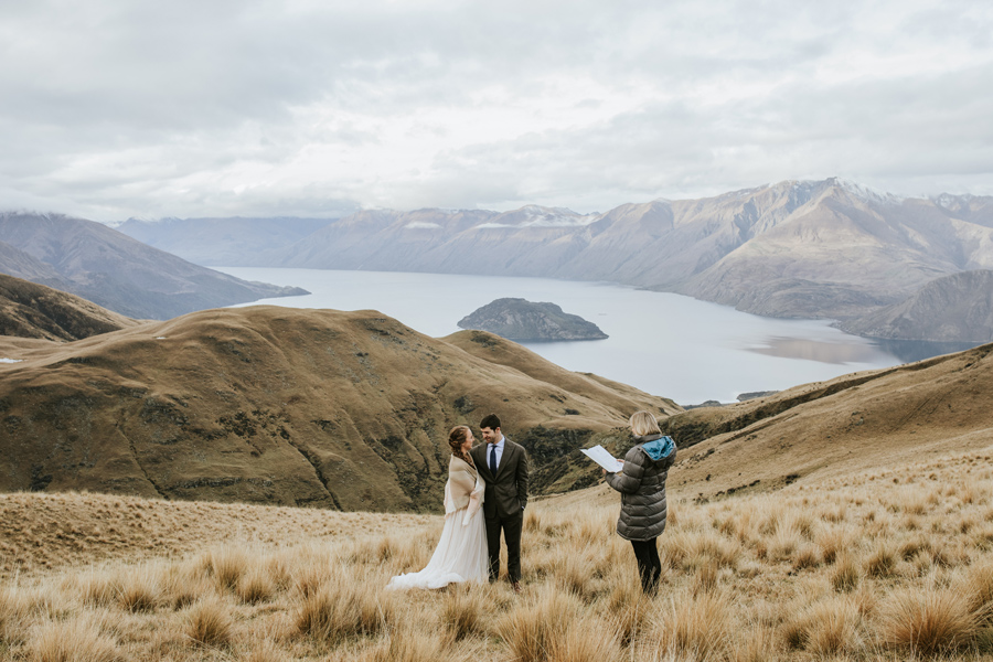 A bride and groom and their celebrand stand together on a mountain overlooking a lake. The celebrant conducts a ceremony for them, in which they will be married. There is a lake and mountains in the distance, and the skies are cloudy.