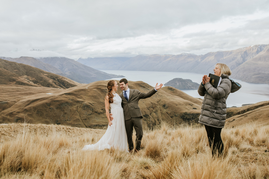 A bride and groom celebrate as they are pronounced husband and wife! They are on a mountain top and the lake and mountains are behind them.
