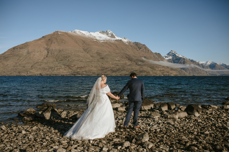 A couple walk hand in hand towards a lake on their wedding day. There are mountains in the background and it is a beautiful sunny day.
