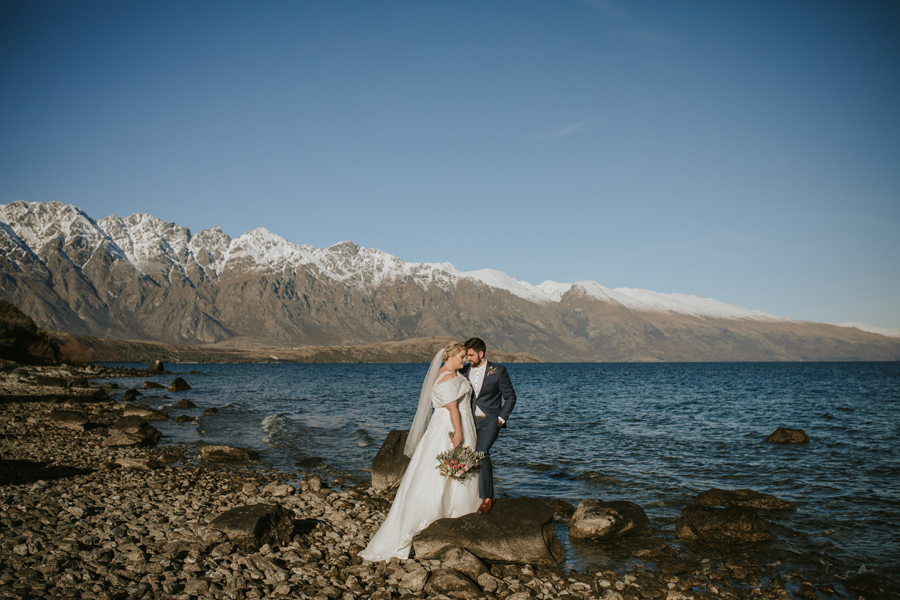 A gorgeous bride and groom embrace as they stand by Lake Wakatipu on their wedding day. The Remarkables mountain range sits in the distance.