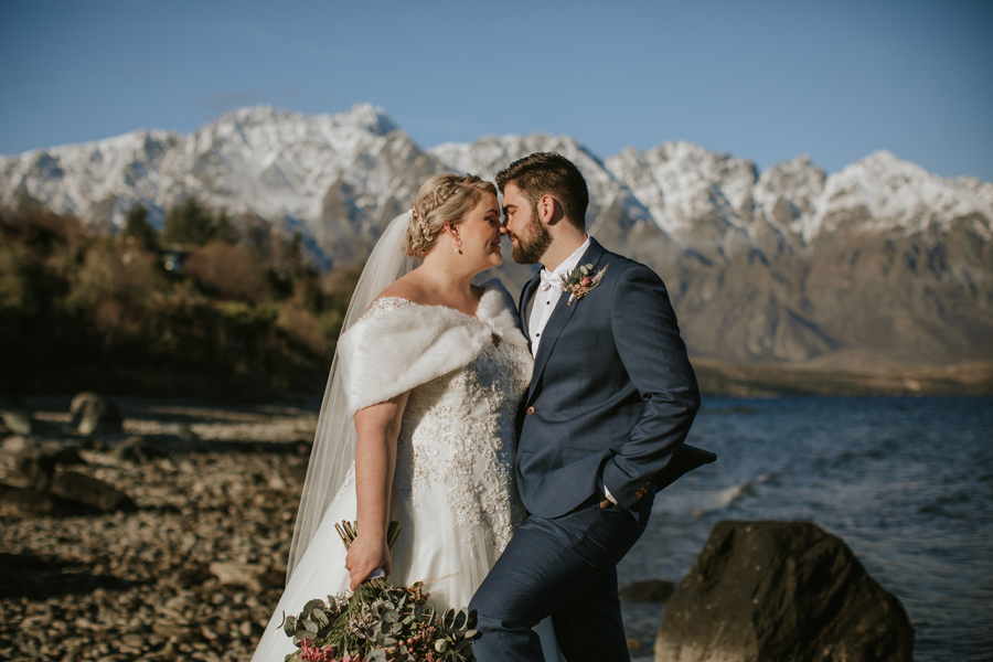 A couple rub their noses together romantically on their wedding day. They are standing beside a Queenstown lake, with a beautiful mountain range in the background.