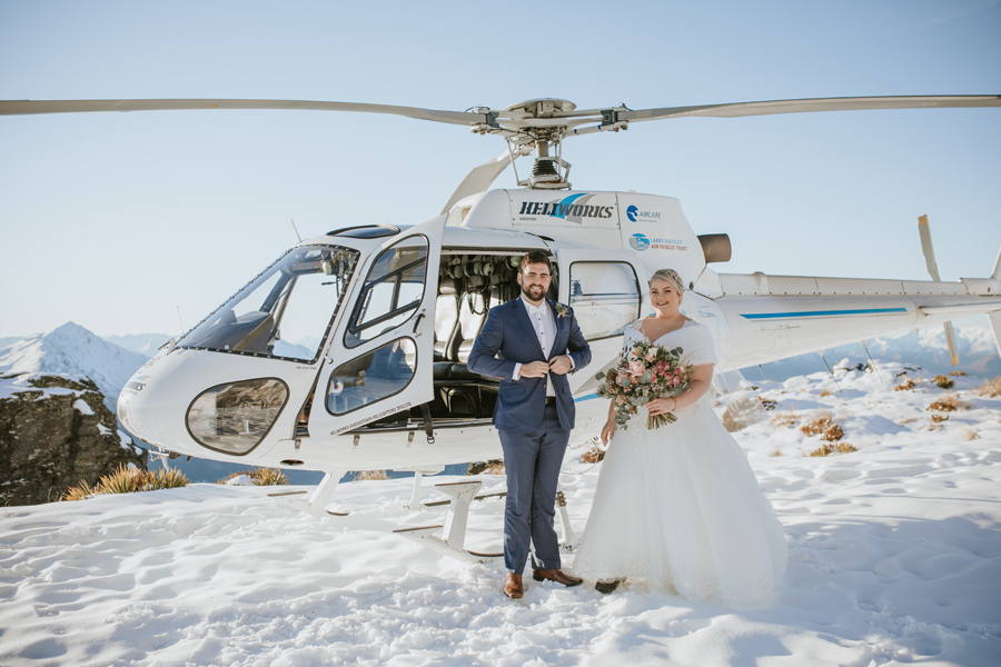 A bride and groom stand by a helicopter on their wedding day. They smile at the camera. They are standing on top of a snowy mountain on a bright blue sky day.