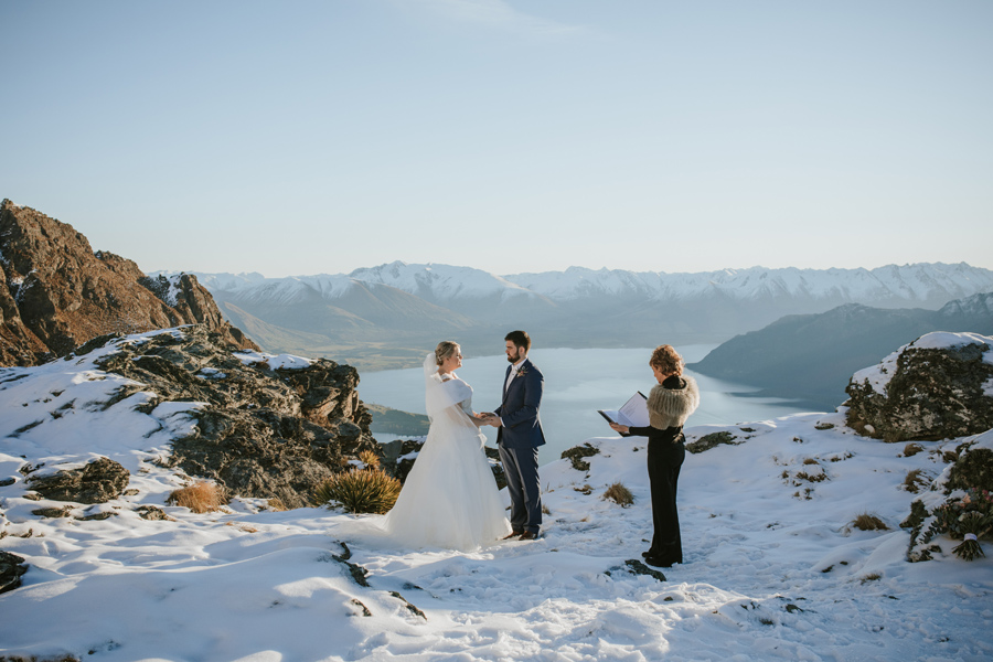 A couple speak their vows to each other on their wedding day. They are standing on a mountain with a lake in the background down below. It is a beautiful blue sky day and the ground is covered in snow.