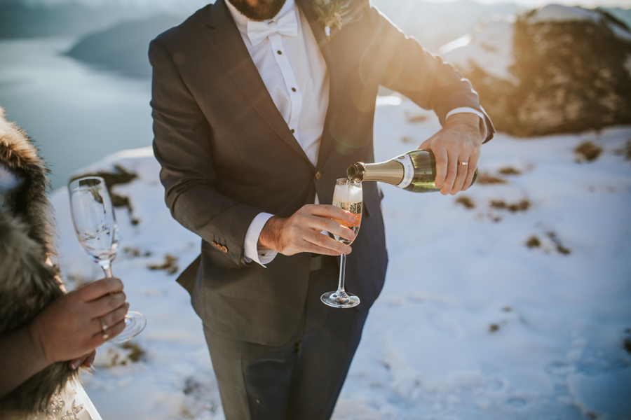 A groom pours champagne into a glass on his wedding day.
