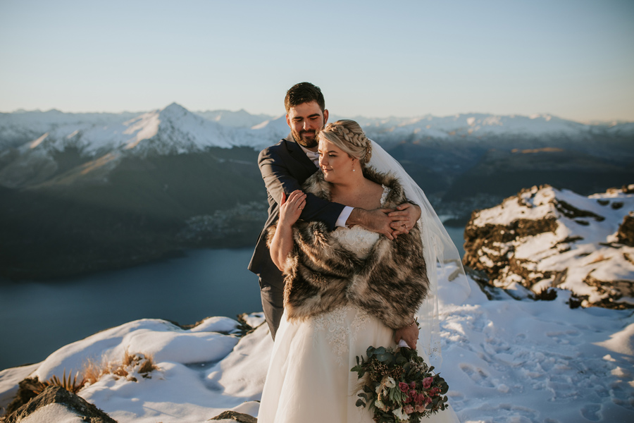 A bride and groom embrace on Cecil Peak, on their winter elopement wedding day.