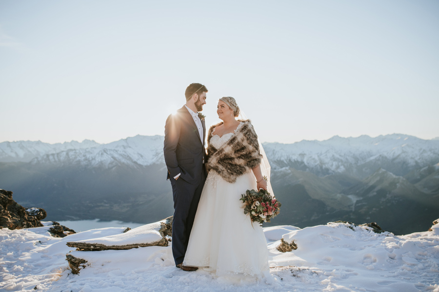 A bride and groom smile at each other as they stand on Cecil Peak on a winters evening. The sun is setting behind them and there is snow on the ground.