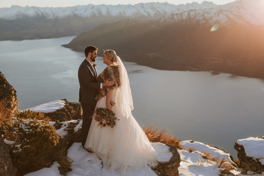 A bride and groom embrace on a mountain top called Cecil Peak in Queenstown. It is a winters day and there is snow on the ground.