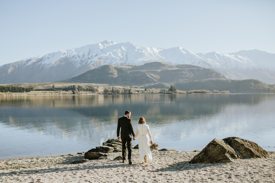 A bride and groom walk towards Lake Wanaka on their wedding day. The sky is blue, there are snow capped mountains in the background and the lake is glassy. With photography by Alpine Image Company