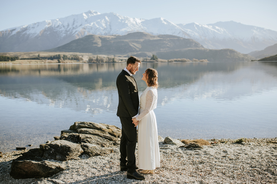 Donna and Michael take a moment together beside Lake Wanaka on their Lake Wanaka Wedding. The mountains behind them are snow capped, and the lake is calm. With photography by Alpine Image Company