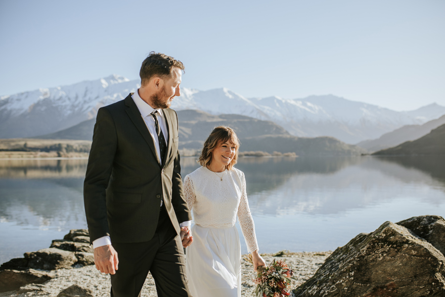 Donna and Michael laugh together as they walk towards the camera on their Lake Wanaka wedding day. They are framed by beautiful blue skies, snow capped mountains and a calm lake. With photography by Alpine Image Company
