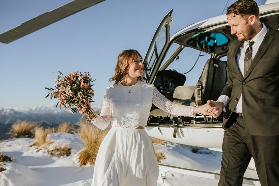 Donna and Michael get out of the helicopter on their Wanaka Wedding Day. With photography by Alpine Image Company