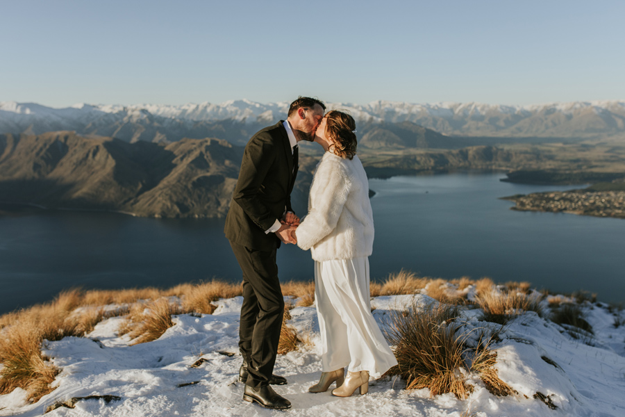 Donna and Michael share their first kiss on top of Coromandel Peak on their Wanaka Wedding Day. The lake below them is calm and the mountains that surround them are snowcapped. With photography by Alpine Image Company