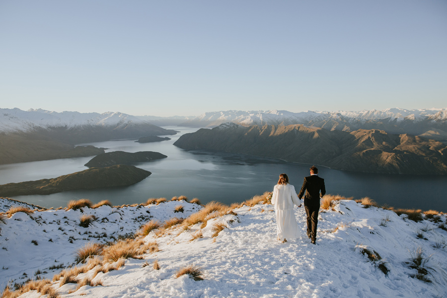 Donna and Michael take a walk on Coromandel peak after their Wanaka Wedding Ceremony. They are surrounded by snow capped mountains and the Lake Wanaka is glassy. With photography by Alpine Image Company