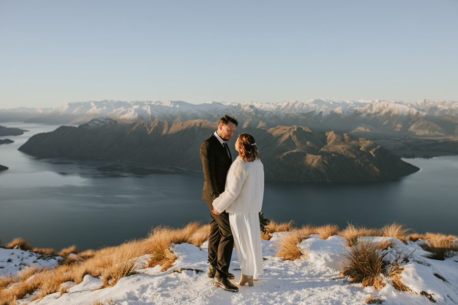 Donna and Michael share an intimate moment on their mountaintop wedding. There is snow on the ground and the sky above them is blue. The mountains are snow capped and the lake is calm. What a stunning day. With photography by Alpine Image Company
