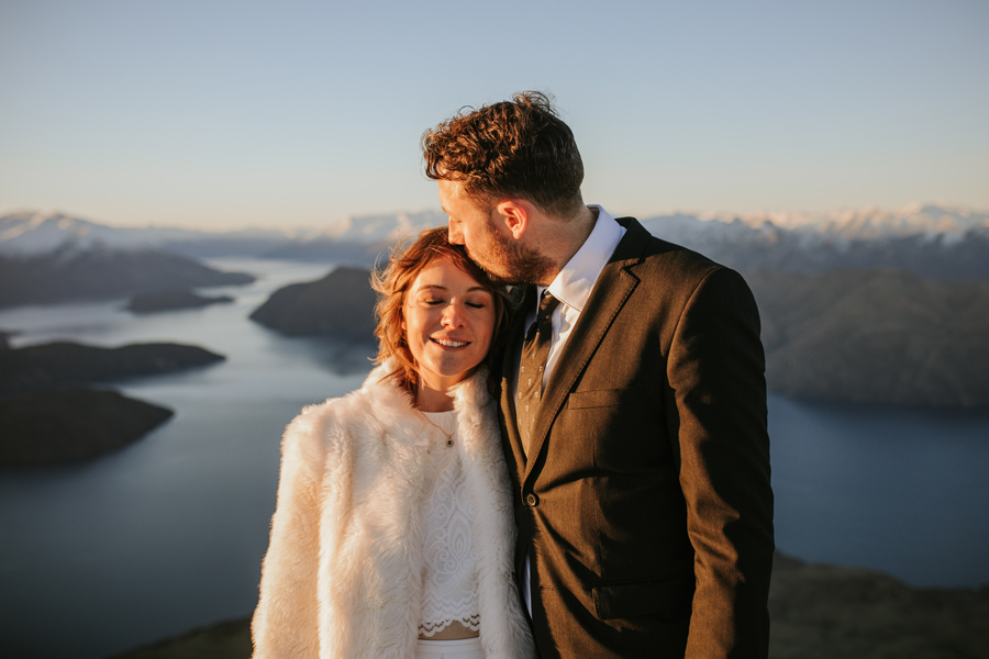 Donna and Michael share an intimate kiss on their Wanaka Wedding Day. They are standing on a mountain top with views of lakes and mountains all around. With photography by Alpine Image Company