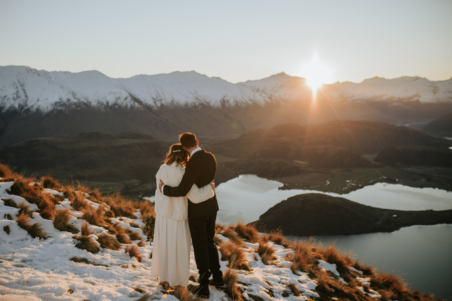 Donna and Michael embrace as they watch the last of the sun set behind the mountains above Lake Wanaka. They are bathed in golden light, and the snow capped mountains that surround them look magestic and beautiful. With photography by Alpine Image Company