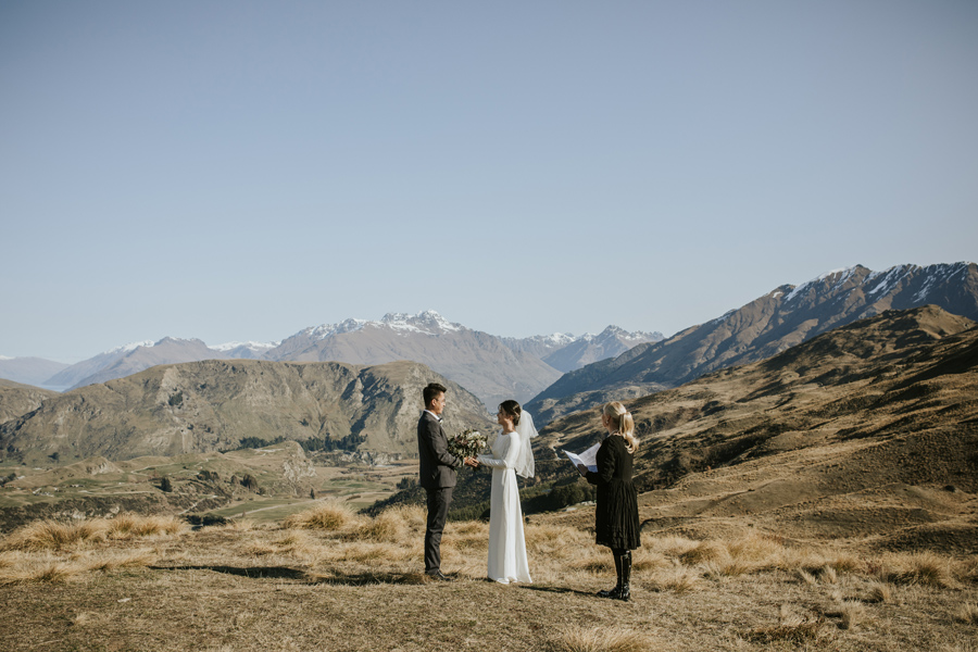 A bride and groom stand together on their mountain top ceremony. It is a beautiful blue sky day and the mountains and the lake are in the distance. With photography by Alpine Image Company.