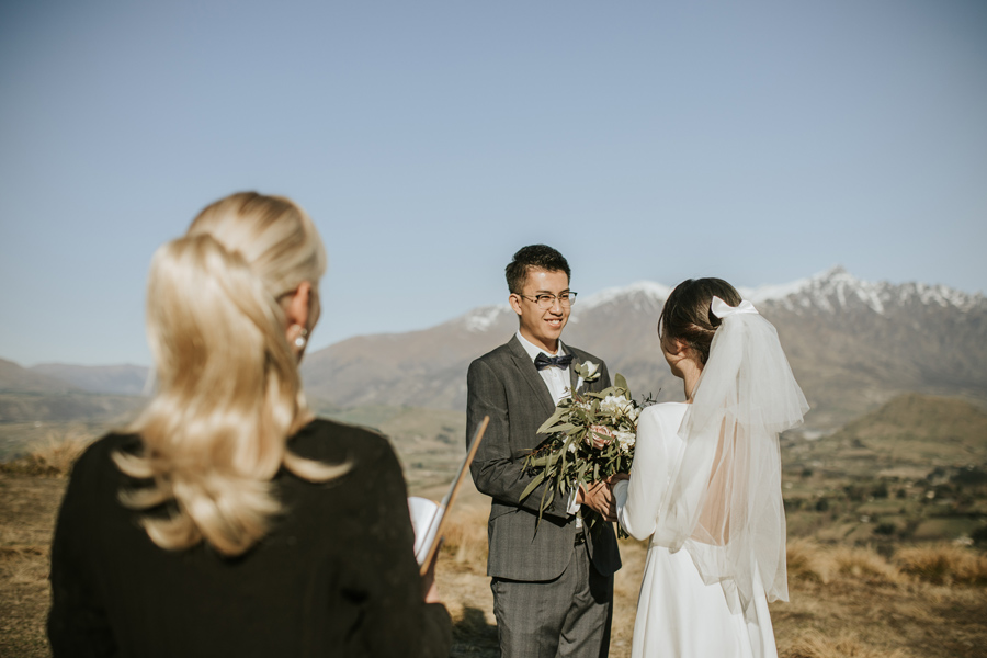 A groom looks lovingly at his bride during their wedding ceremony on Coronet Peak, Queenstown.  With photography by Alpine Image Company