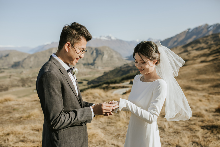A couple exchange rings on their mountain top ceremony. The bride smiles happily as the groom places the ring on her finger.  With photography by Alpine Image Company