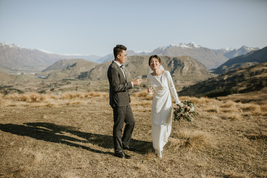 A bride and groom laugh together as they celebrate their first glass of bubbles as husband and wife after their mountain top ceremony. The sky is blue and the mountains surrounding them look spectacular.  With photography by Alpine Image CompanyWith photography by Alpine Image Company