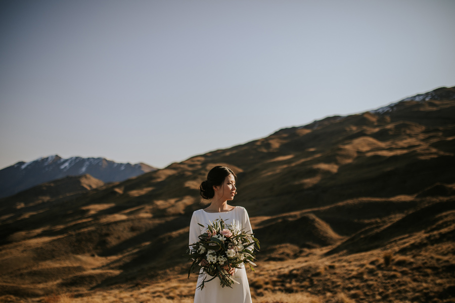 A stunning bride gazes out at the view. She stands on a mountain on her wedding day, holding a stunning bouquet of flowers.  With photography by Alpine Image Company