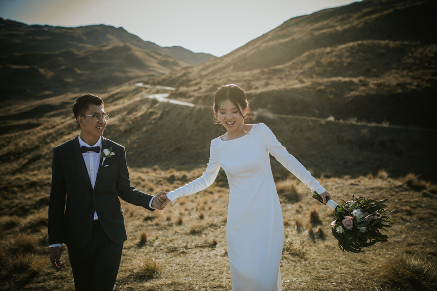 A bride and groom walk together in the mountains on their wedding day. The sun sets behind them and the light on the mountains looks incredible.  With photography by Alpine Image Company