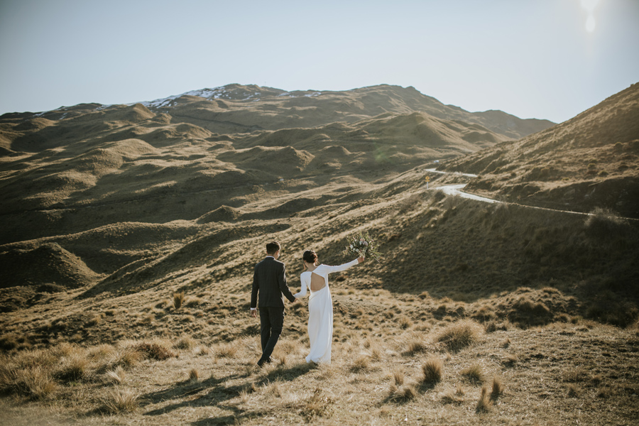A bride and groom walk away from the camera. They are in the mountains and the last of the days light is creating wonderful shadows on the hills that they walk towards.  With photography by Alpine Image Company