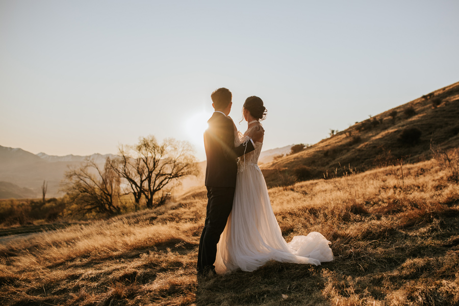 A couple embrace as the sun sets behind them. The light that surrouns them is golden, and they look towards the setting sun.  With photography by Alpine Image Company