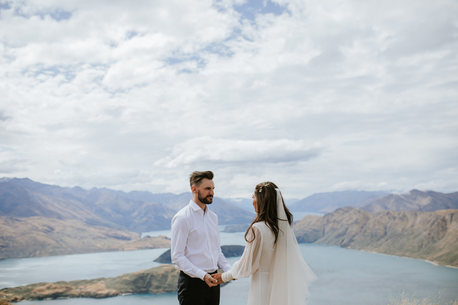 A stunning bride and groom hold hands on Mount Roy, during their wedding ceremony. Lake Wanaka sits behind them, and they are surrounded by green mountains.