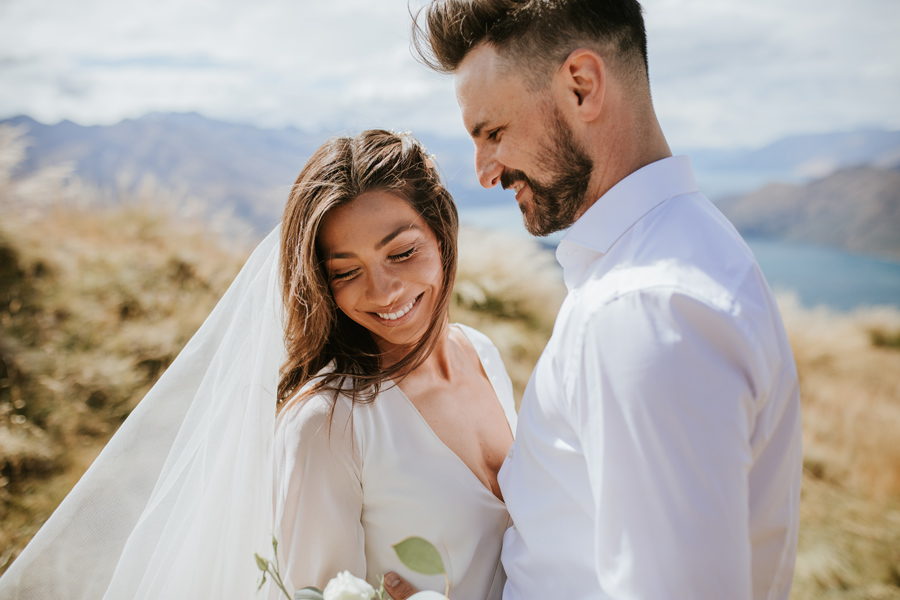 Briana and Rob cuddle up to each other during their mountain wedding. The soft summer sun creates a warm glow around them as they laugh together. Mountains and lakes surround them, and they stand in a field of long golden grass. With photography by Alpine Image Company