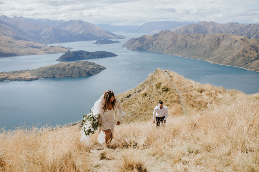 Briana and Rob hike up Mount Roy on their wedding day, in their wedding clothes! The view behind them is spectacular, with lakes and mountains as far as the eye can see. With photography by Alpine Image Company