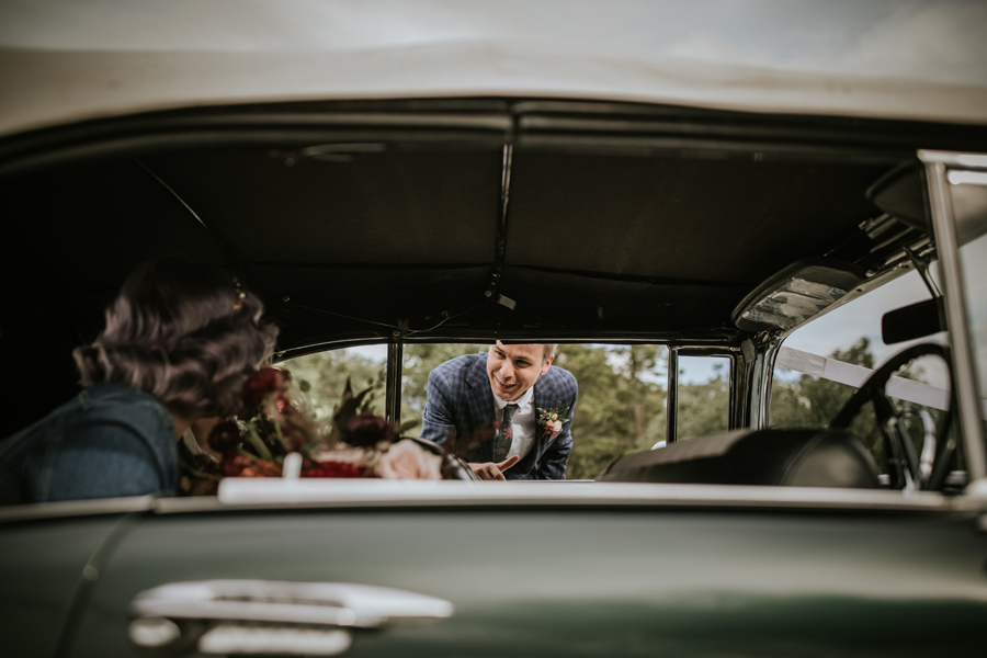 A groom look in through the open window of his 1950s soft top car. He sees his wife in the back and smiles. With photography by Alpine Image Company