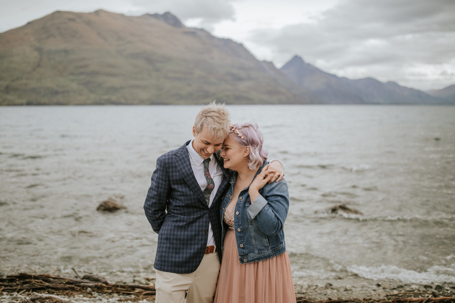 A bride and groom share a moment after their Queenstown lakeside ceremony. The lake and mountains are in the background. With photography by Alpine Image Company
