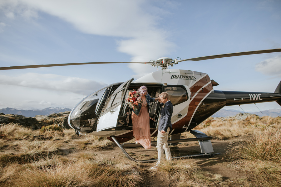 A groom helps his bride out of the helicopter on their Queenstown wedding day. With photography by Alpine Image Company
