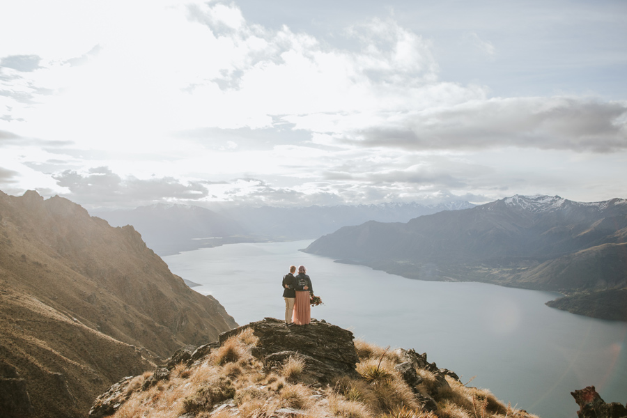 A bride and groom hold each other as they look out onto mountains and a blue lake, on their Queenstown wedding day. With photography by Alpine Image Company