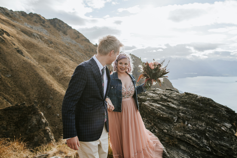 A bride smiles at her groom as he leads her by the hand on a rocky mountain top. There is a blue lake, and mountains in the background. With photography by Alpine Image Company