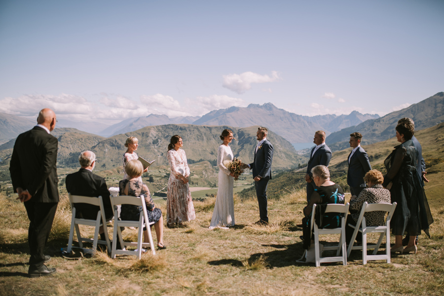 A bride and groom hold hands in front of their guests on their wedding ceremony. They are getting married on a mountainside in Queenstown. There are mountains and a lake in the distance, and the sky is blue. With photography by Alpine Image Company