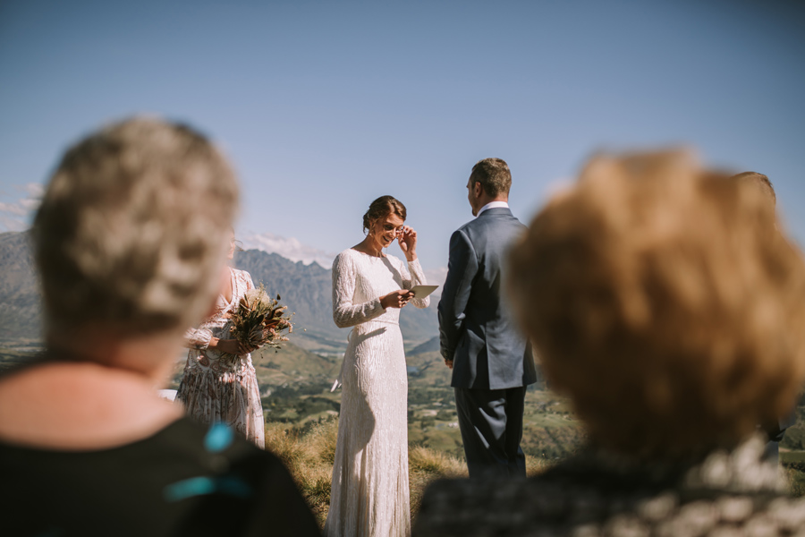 A bride dabs away a tear as she reads her vows to her groom on her Queenstown wedding day. With photography by Alpine Image Company
