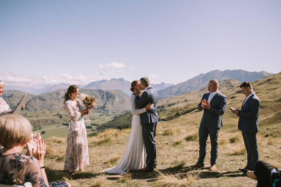 A couple share their first kiss. The bridal party clap. They are standing on a mountainside and there are mountains in the background. With photography by Alpine Image Company