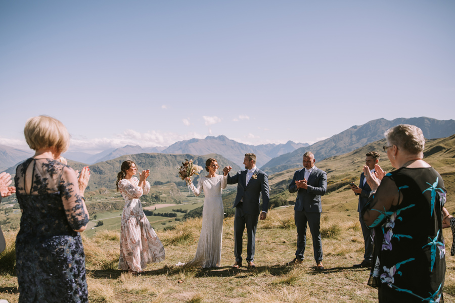A bride and groom celebrate with their guests as their wedding ceremony finishes. They are standing on a mountainside, with mountains and a lake in the background. With photography by Alpine Image Company