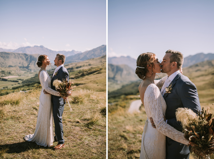 A bride and groom embrace, and share a kiss on their Queenstown wedding day. They are standing on Coromandel Peak, and there are mountains and a blue sky behind them. With photography by Alpine Image Company