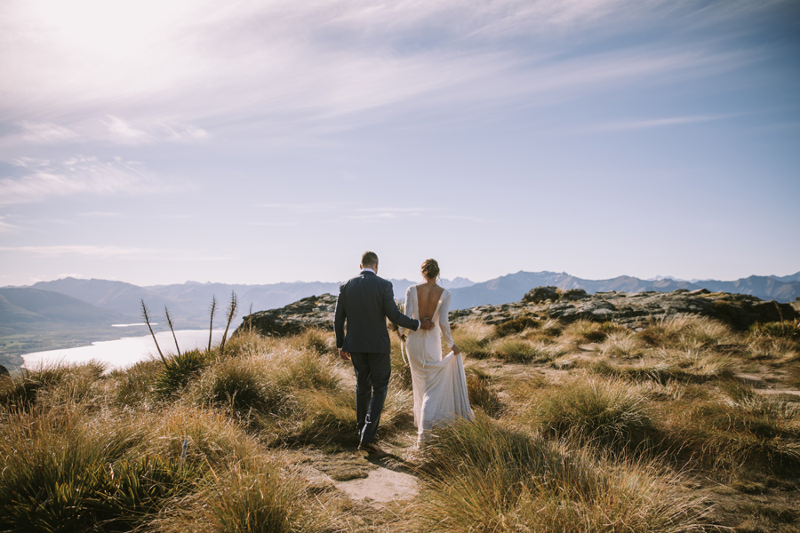 A groom leads his bride gently away from the camera. They are walking on a mountain top, and there are mountains and a lake behind them. The sky is blue, and they walk through tussock grass. With photography by Alpine Image Company