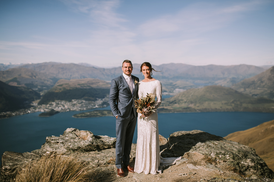 A bride and groom smile at the camera. They are standing on a mountain top on their Queenstown wedding day. Queenstown is behind them. They look out over a lake and mountains in the distance. With photography by Alpine Image Company