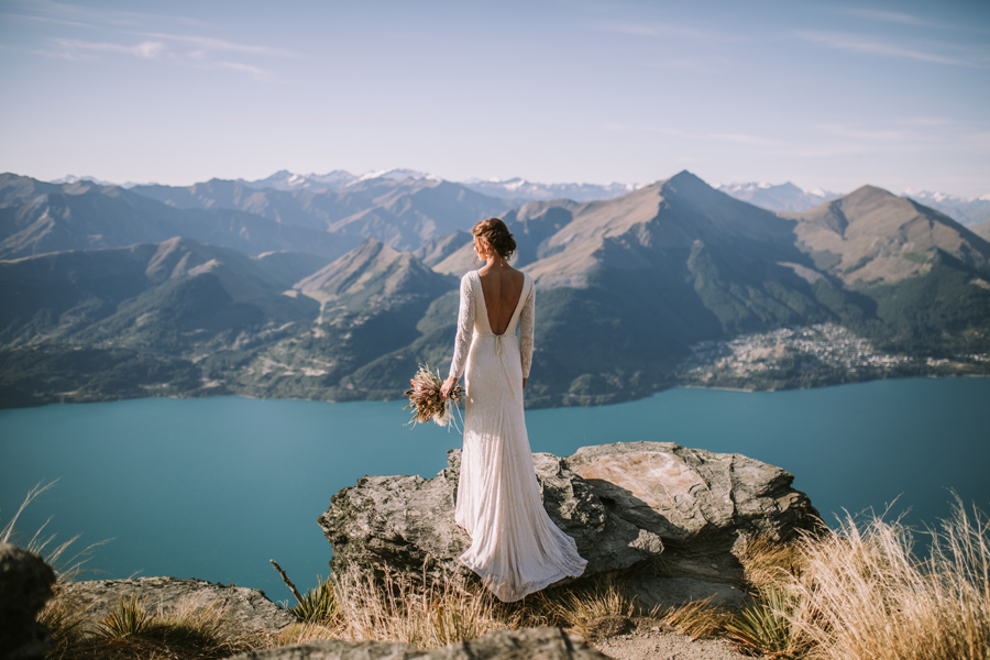 A bride looks out at a spectactular view on her wedding day. She stands on a rock, and there is a lake and mountains in the distance. With photography by Alpine Image Company
