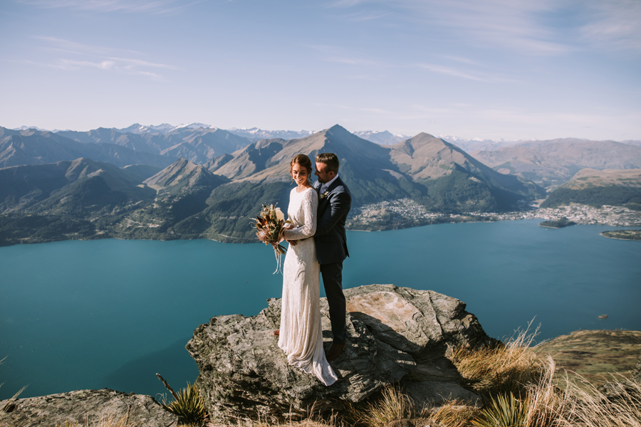 A bride and groom embrace on a mountain, on their Queenstown wedding day. There is a lake and mountains behind them. The sky is blue. With photography by Alpine Image Company